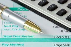 Pluma, calculadora y hoja de paga Foto de archivo