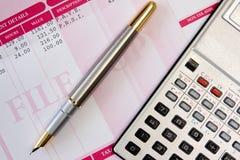 Pluma, calculadora y hoja de paga de la tinta Imágenes de archivo libres de regalías