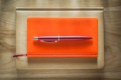 Pluma cerrada del biro de las libretas en el tablero de madera imagen de archivo libre de regalías