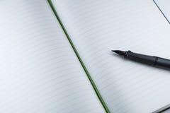 Pluma con el blanknotebook Foto de archivo libre de regalías
