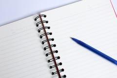Pluma con el cuaderno con el libro en la tabla blanca Fotos de archivo libres de regalías