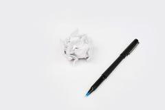 Pluma con la hoja de papel arrugada para empapelar la bola en el fondo blanco Foto de archivo libre de regalías