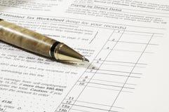 Pluma con la hoja de trabajo del impuesto Imagen de archivo libre de regalías