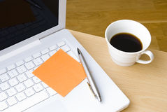 Pluma con la nota de post-it, la computadora portátil y la taza de café Foto de archivo libre de regalías