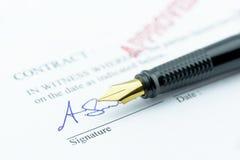 Pluma con una firma en un contrato aprobado imagenes de archivo