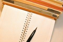 Pluma, cuaderno con las páginas en blanco y libros viejos imagen de archivo