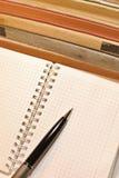 Pluma, cuaderno con las páginas en blanco y libros viejos fotografía de archivo