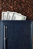 Pluma, cuaderno de cuero hermoso y granos de café El hombre de negocios vende el café Imágenes de archivo libres de regalías