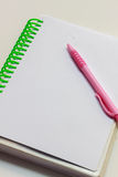 Pluma, cuaderno en el fondo blanco Fotografía de archivo libre de regalías