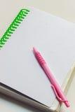 Pluma, cuaderno en el fondo blanco Fotografía de archivo