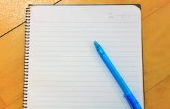 Pluma, cuaderno en el fondo de madera Foto de archivo libre de regalías