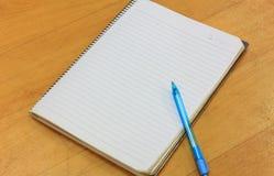 Pluma, cuaderno en el fondo de madera Fotografía de archivo