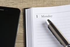 Pluma de Îœetal en un calendario y un smartphone Fotografía de archivo libre de regalías