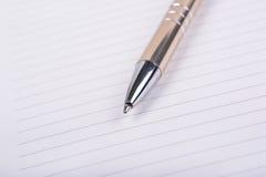 Pluma de bola en la hoja en blanco del cuaderno imagen de archivo libre de regalías