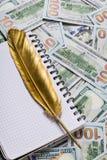 Pluma de canilla del cuaderno y del oro en fondo del dinero del dólar fotografía de archivo libre de regalías