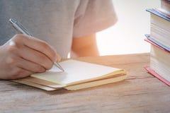 Pluma de la escritura del hombre en libro foto de archivo