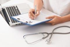 Pluma de la plata del control de la mano del doctor que llena la lista de la historia paciente en el clip foto de archivo