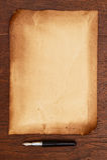 Pluma de la tinta y pergamino de papel envejecido Foto de archivo libre de regalías