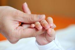 Pluma de los niños en las manos de dedos adultos Imágenes de archivo libres de regalías