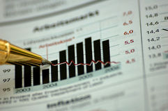 Pluma de oro que muestra el diagrama en informe financiero Foto de archivo libre de regalías