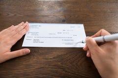 Pluma de Person Hands Signing Cheque With Imágenes de archivo libres de regalías