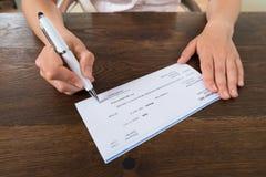 Pluma de Person Hands Signing Cheque With Fotos de archivo libres de regalías