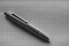 Pluma de plata en el papel de la rejilla Fotografía de archivo