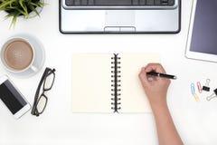 Pluma de tenencia de la mano con el cuaderno abierto del espacio en blanco Fotos de archivo