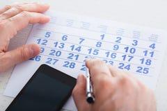 Pluma de tenencia de la mano en calendario foto de archivo