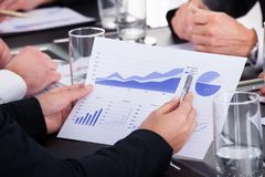 Pluma de tenencia del hombre de negocios sobre gráfico en la reunión de negocios Foto de archivo