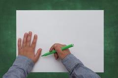 Pluma de tenencia del niño en la hoja de papel en blanco Imagen de archivo