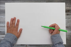 Pluma de tenencia del niño en la hoja de papel en blanco Fotografía de archivo