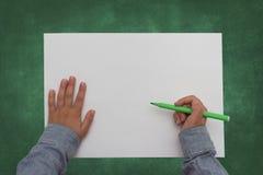 Pluma de tenencia del niño en la hoja de papel en blanco Imagen de archivo libre de regalías