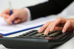 Pluma de tenencia femenina de la mano del contable que cuenta en la calculadora Foto de archivo libre de regalías