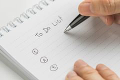 Pluma de tenencia de la mano que escribe qué hacer en personal para hacer el cuaderno de notas de la lista en la tabla blanca usa fotos de archivo libres de regalías
