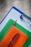 Pluma del biro de los cuadernos del tablero en el tablero de madera foto de archivo