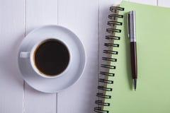 Pluma del cuaderno del café en fondo de madera foto de archivo