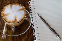 Pluma del cuaderno y taza de café Fotos de archivo