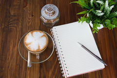 Pluma del cuaderno y taza de café Foto de archivo