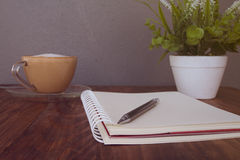 Pluma del cuaderno y taza de café Imágenes de archivo libres de regalías