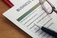 pluma del foco selectivo, formulario de inscripción de préstamo empresarial, vidrios, pape Foto de archivo