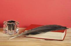 Pluma del libro viejo y de canilla con el tintero en la tabla de madera Espacio de la copia libre imagenes de archivo