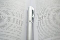Pluma del negocio en un libro abierto Foto de archivo libre de regalías