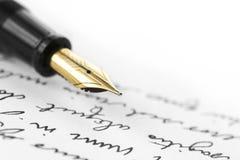 Pluma del oro en letra escrita mano Imagen de archivo libre de regalías