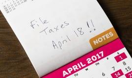 Pluma del oro que pone en el calendario para el día del impuesto Foto de archivo