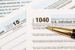 Pluma del oro que pone 2015 la forma 1040 del IRS Imagen de archivo libre de regalías