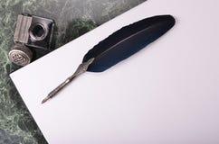 pluma del vintage y tinta azul en el papel Fotografía de archivo libre de regalías