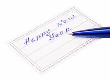 Pluma e insignia con la Feliz Año Nuevo de la inscripción Fotografía de archivo libre de regalías