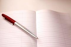 Pluma en el cuaderno Foto de archivo libre de regalías