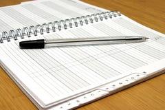 Pluma en el cuaderno. Foto de archivo libre de regalías